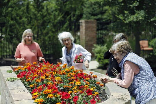 Nancy Moore, front right, Sandra Harper, right back, Marilyn Haradine, middle back, and Jane Vanover, back left, look over the garden outside of the Senior Star's memory wing at the Dublin Retirement Village in Dublin, Ohio on June 25, 2020.  The outdoor destination stations help their cognitive abilities improve after the inside destinations were closed because of the pandemic.