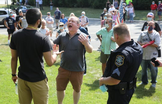 Eric Cohen, right, debates a member opposing the Columbus monument. Citizens staged a demonstration on Rt. 46 in support of a protecting a bust of Christopher Columbus that stands outside the Parsippany municipal building. A group opposing the monument gathered on the same grounds and each group debated one another.