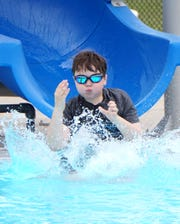 Jude Madson, 10, splash-slides into Livonia's Clements Circle Pool on June 26, 2020.