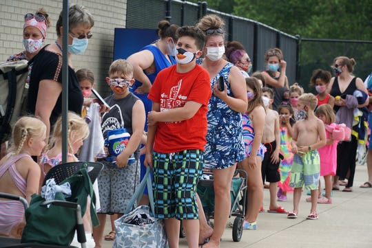 Visitors to Livonia's Clements Circle Pool, most in face coverings, line up on June 26, 2020 as it opens for the season.