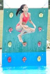 Tessa White, 10, leaps off a climbing board into the Clements Circle Pool.