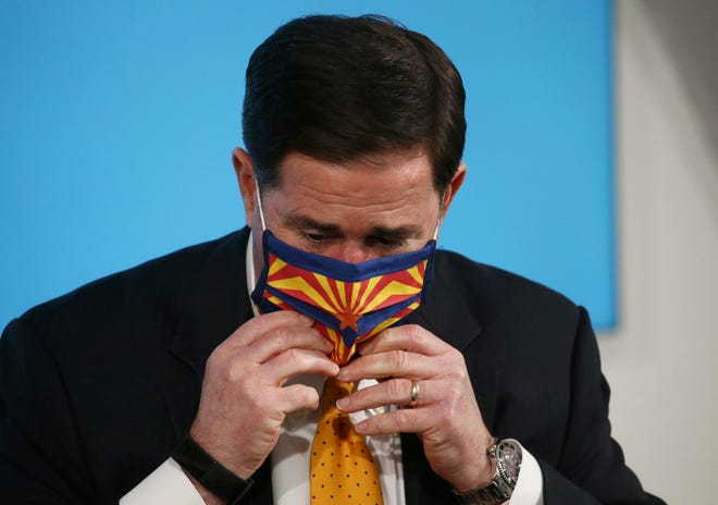 Arizona Gov. Doug Ducey puts a face covering back on after speaking about the latest coronavirus data at a news conference on June 25, 2020, in Phoenix.