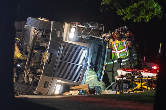 "Firefighter Ken Kuhn, right, alongside other firefighters, uses a hydraulic cutter - ""the jaws of life"" - to flap the roof off of a rolled grain truck while trying to extricate the entrapped driver on the 700 block of Moul Avenue, early Friday, June 26, 2020, in Hanover Borough. The sole occupant of the truck, the driver, was flown to York Hospital for a head injury, said Hanover Area Fire & Rescue Chief Tony Clousher."