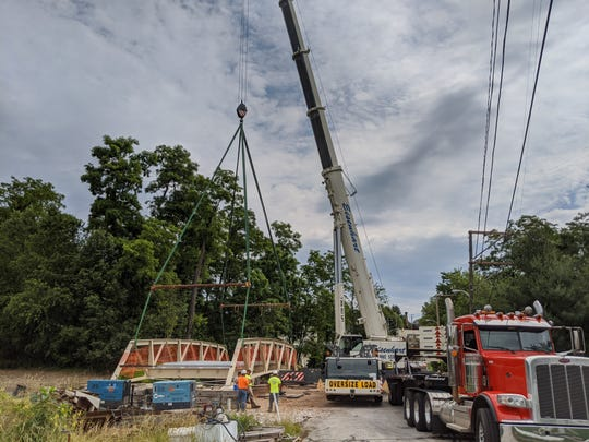 Crews set a rehabilitated historic bridge truss back into place on Singer Road in New Freedom on Thursday over the county's rail trail. The span, built in 1905, became eligible to be listed on the National Register of Historic Places in 2017. It is one of the dwindling number of Warren truss bridges in Pennsylvania, according to C.S. Davidson, Inc.