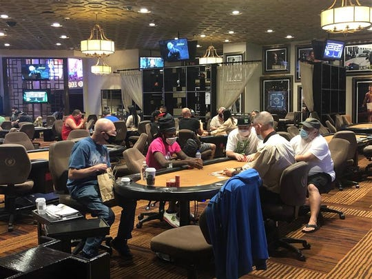 In the poker room at Caesars Palace, the day Nevada Gov. Steve Sisolak's mask order went into effect, everyone packed the tables played with shielded faces.