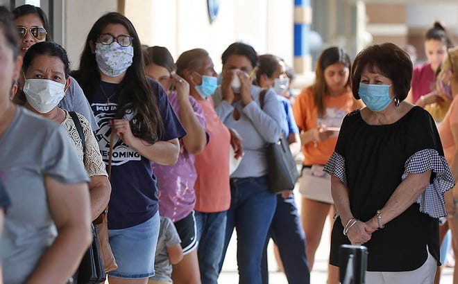 A group of people wearing face masks wait in line to get into the Ross Dress for Less store in San Angelo on Wednesday, May 20, 2020.