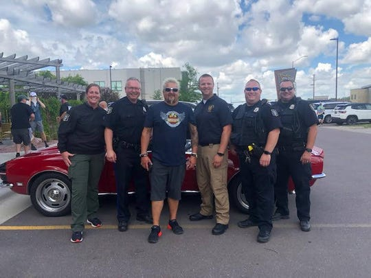 Guy Fieri, host of Diners, Drive-Ins and Dives, poses with officers from the Sioux Falls Police Department. This photo was shared on the department's Twitter account Friday.
