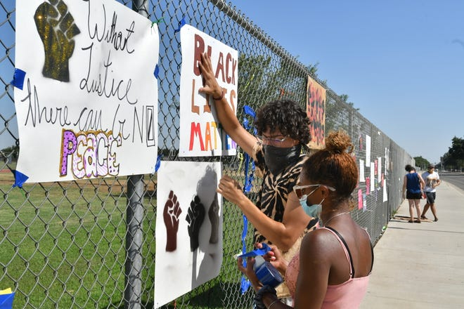 Visalia youth and students replace vandalized Black Lives Matter signs at El Diamante High School on June 25, 2020.