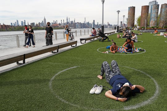 People relax in circles marked on the grass for proper social distancing at Brooklyn's Domino Park, Monday, May 18, in New York, during the current coronavirus outbreak. The circles were added after the park, which has excellent views of the Manhattan skyline, became severely overcrowded during a spate of warm weather just over a week ago.