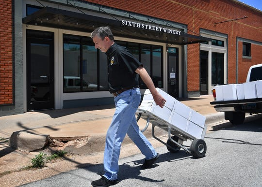 Bill Anderson, owner of Sixth Street Winery in downtown Wichita Falls, brings in a load of bottles Friday. Texas Gov. Greg Abbott announced Friday morning his order to close bars and scale back restaurant occupancy due to high infection rates of COVID-19.