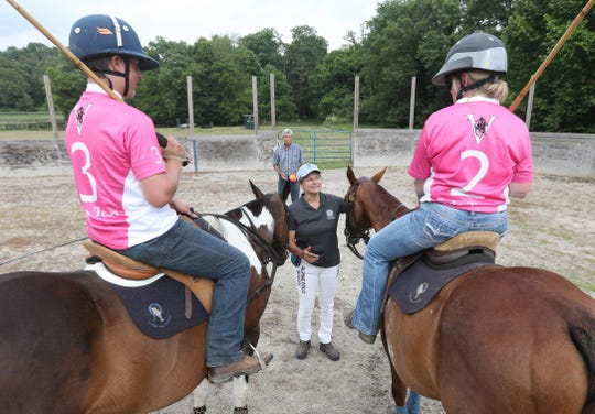 Sheila Everett gets ready to start a polo match Dylan Starner, left and his aunt Debbie Earnest. Holding the polo balls behind her is her husband Troy. The Everetts run Alpine Polo School in Frazeysburg.