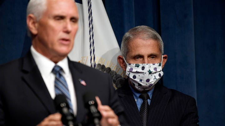 Dr. Anthony Fauci, right, director of the National Institute of Allergy and Infectious Diseases, listens as Vice President Mike Pence speaks during a news conference with the Coronavirus task force at the Department of Health and Human Services in Washington, Friday, June 26, 2020. (AP Photo/Susan Walsh)