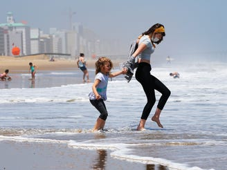 In this May 22, 2020, file photo, Victoria Faughnan, right, and Evelyn Faughnan, play in the surf in Virginia Beach, Va., the day the state reopened the beachfront during the coronavirus pandemic. The pandemic not only upended the tourism industry, but how states, cities and attractions market themselves as summer travel destinations.