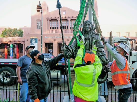 Workers fit harnesses around a statue of Don Diego de Vargas during the statue's removal from Cathedral Park in Santa Fe, N.M., Thursday, June 18, 2020. (Matt Dahlseid/Santa Fe New Mexican via AP)
