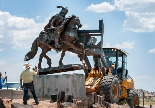 Rio Arriba County workers remove the bronze statue of Spanish conquerer Juan de Oñate from its pedestal in front of a cultural center in Alcalde, N.M., Monday, June 15, 2020. Crowds of people for and against the removal lined Highway 68 near of the center. (Eddie Moore/The Albuquerque Journal via AP)