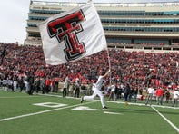 A Texas Tech Red Raiders cheerleader enters the field before a game against the the Texas Christian Horned Frogs at Jones AT&T Stadium.