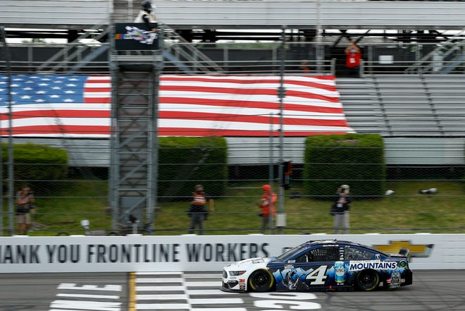 Kevin Harvick takes the checkered flag as he crosses the finish line to win a NASCAR Cup Series  race at Pocono Raceway on Saturday in Long Pond, Pa. MATT SLOCUM/AP