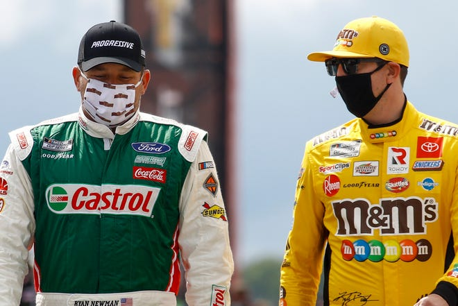 Ryan Newman, left and Kurt Busch walk down pit row down before the start of Saturday's NASCAR race at Pocono Raceway. MATT SLOCUM/AP
