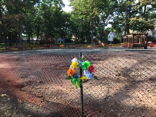 A wreath was hung on fencing that wrapped around the site where the OurSpace Playground once stood, pictured on June 26, 2020.