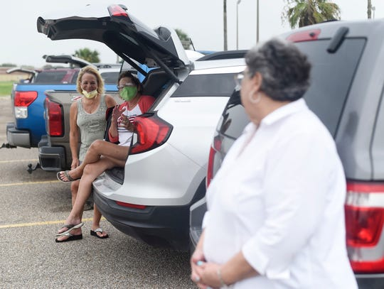 Sandra Drews, far left, Sherri Erwin, middle, and Diana Rojos sit in their cars while they wait for their COVID-19 test, Saturday, June 27, 2020, in Portland. Drews and Erwin drove from Aransas Pass for their test.