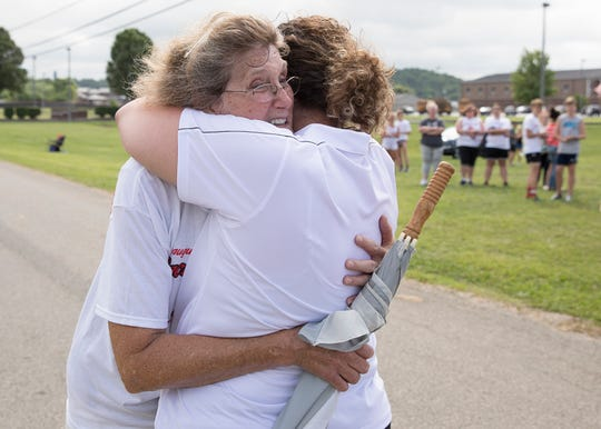 Denise Orr hugs Kim Moore after she finished walking the Zach Farmer 5K race. Orr, who was in a bad automobile accident in 2018, almost had her leg amputated but was able to save it and finish the race with the help of family.