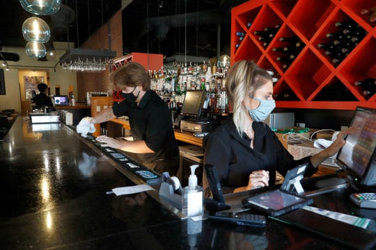 Deep Sushi restaurant employees Jordan Arrowood, left, cleans the bar top as Carrie Souza enters an order at the sushi restaurant in the Deep Ellum entertainment district in Dallas, Friday, June 26, 2020.