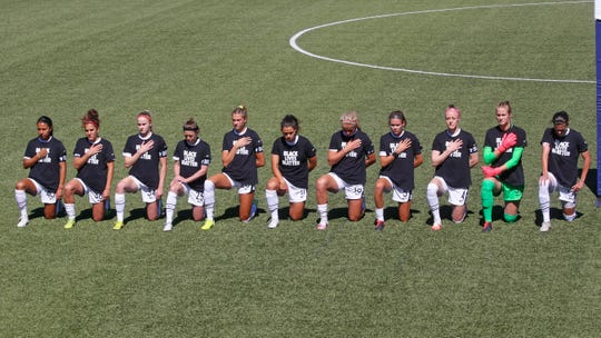 Players for the Portland Thorns kneel during the national anthem before the start of their NWSL Challenge Cup soccer match against the North Carolina Courage at Zions Bank Stadium Saturday, June 27, 2020, in Herriman, Utah.