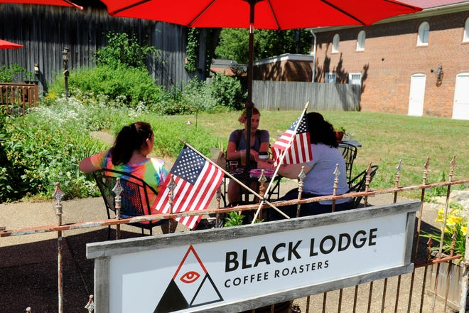 Customers enjoy a drink outside Black Lodge Coffee Roasters in New Harmony on Tuesday, June 16, 2020. Beginning March 13, enjoy a charcuterie box by Board & Wheel with your coffee drink.