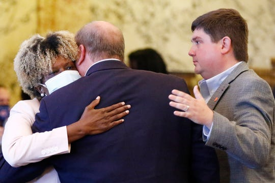 Sen. Sarita Simmons, D-Cleveland, left, hugs, Republican Sen. Brice Wiggins, of Pascagoula, center, and Jeremy England, of Vancleave, following the body passing a resolution that would allow lawmakers to change the state flag Saturday, June 27, 2020, at the Capitol in Jackson, Miss. Members of both the House and Senate are now expected to pass a bill that removes the current flag and establishes a path forward to getting a new one. Gov. Tate Reeves has already said he would sign whatever flag bill the Legislature decides on. The current flag has in the canton portion of the banner the design of the Civil War-era Confederate battle flag, that has been the center of a long-simmering debate about its removal or replacement. (AP Photo/Rogelio V. Solis)
