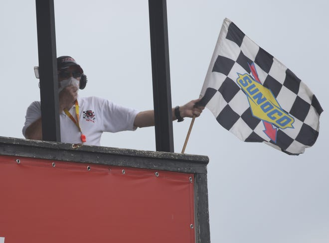 A starter at Mid-Ohio Sports Car Course waves the checkered flag as the historic road course brought racing back for the first time in 2020 with the Vintage Grand Prix of Mid-Ohio over the weekend.