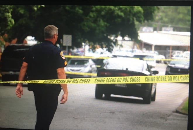 An officer walks past the crime scene tape at the scene of a homicide on Edgewood Boulevard in Franklin, Tennessee, on June 27, 2020.