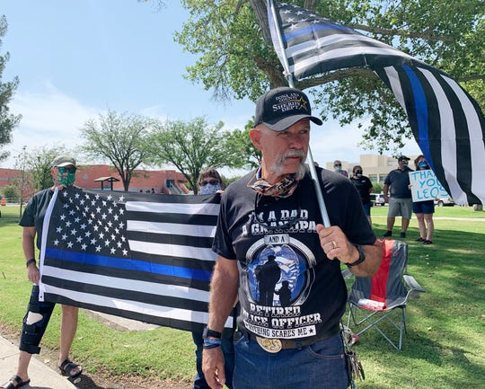 Ben Venable stands in front of family members holding a Back the Blue flag during a rally at Albert Johnson Park, Saturday, June 27, 2020. The retired law enforcement officer said he knew from a young age that he wanted to be a police officer and that two of his sons are now in law enforcement.