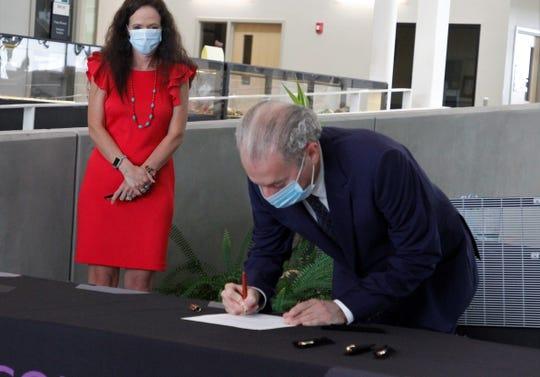 Enchant Energy COO Peter Mandelstam signs a memorandum of understanding, Friday, June 26, 2020, as San Juan College President Toni Hopper Pendergrass watches at the School of Energy in Farmington.