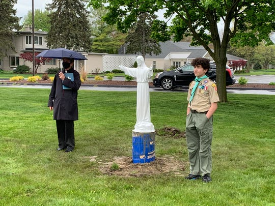 Fr. Jim McNulty, pastor of St Edith Church in Livonia, stands with Andrew Atala, Eagle Scout candidate.