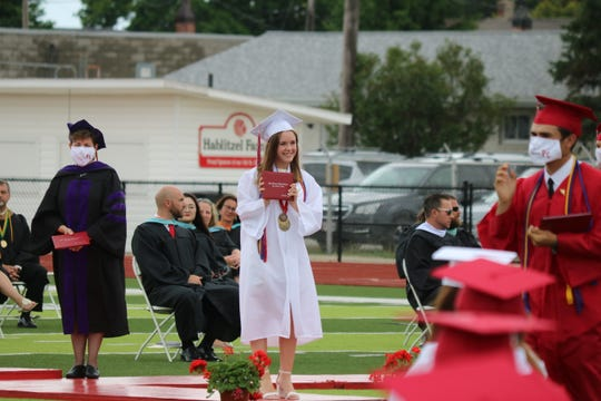 Hannah Moore, of Port Clinton High School's Class of 2020, smiles after receiving her diploma during the 136th annual commencement ceremony at True Lay Stadium on Saturday.