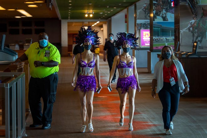 Showgirls Angela Simpkins, left, and Vanessa Harkins, walk to the casino floor minutes before the reopening of the Harrah's Philadelphia Casino and Racetrack in Chester, Pa., Friday, June 26, 2020. (Jose F. Moreno/The Philadelphia Inquirer via AP)