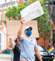 Noel Vega Jr. holds his sign high during the march in support of the Black Lives Matter movement and the LGBTQ community on Saturday, June 27, 2020. The rally, hosted by the Rainbow Rose Center, started at Penn Park and continued through town to Cherry Lane.