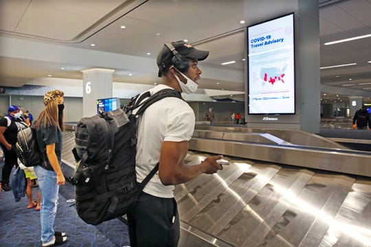 Arriving passengers await their bags in the baggage claim area at LaGuardia Airport's Terminal B baggage claim area, Thursday, June 25, 2020, in New York. New York, Connecticut and New Jersey are asking visitors from states with high coronavirus infection rates to quarantine for 14 days.