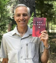 """Retired surgeon Dr. John Harch holds a copy of his new book, """"Red Blanket,"""" which recounts his harrowing surgical training at a hospital in the Los Angeles area in the 1980s."""