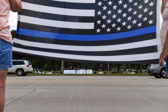 """Counter-protestors lie on the sidewalk opposite two women holding a """"thin blue line"""" flag during a pro-police rally on Saturday, June 27, on 12th Street in Sioux Falls."""