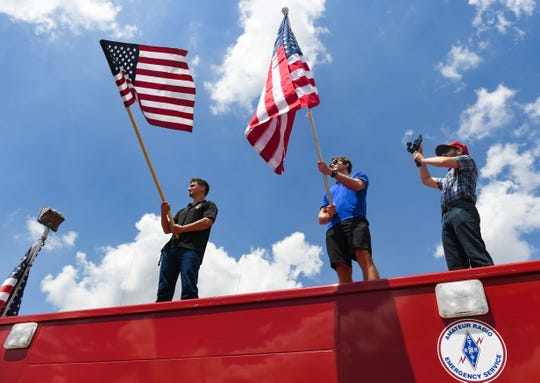 Ryan Shawd and Cole Heisey wave flags at a pro-police rally while standing on a radio station's truck on Saturday, June 27, on 12th Street in Sioux Falls.