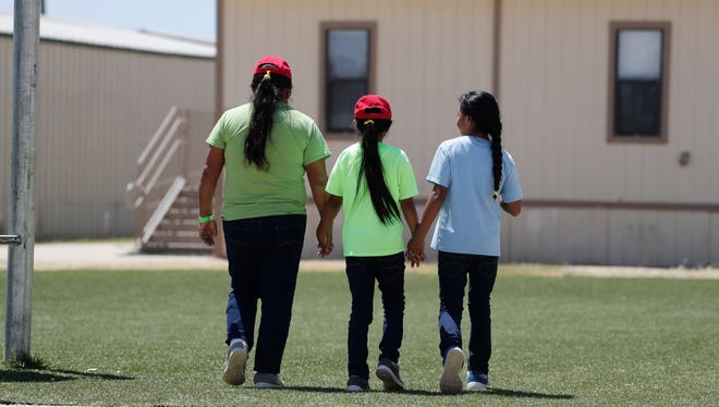 FILE - In this Aug. 23, 2019 file photo, immigrants seeking asylum hold hands as they leave a cafeteria at the ICE South Texas Family Residential Center in Dilley, Texas. The isolation of at least three families at the U.S. Immigration and Customs Enforcement's detention center in Dilley, has raised new fears of the coronavirus spreading through a facility that has long been accused of providing substandard medical care. (AP Photo/Eric Gay, File)