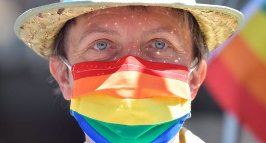 A man wearing a protective mask with rainbow colors takes part in a Pride March in Berlin on June 27, 2020.