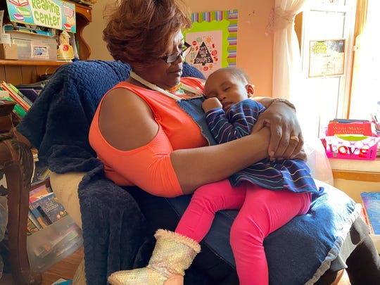 "Child care provider Josephine Smith sits with a sleepy De'ior Hutchins, 2, who she looks after in her home in Muskegon, Michigan. ""I'm serving children, the community and helping parents,"" said Smith of her work. Most of her clients, though not De'ior's mother, pay her through state child care subsidies."