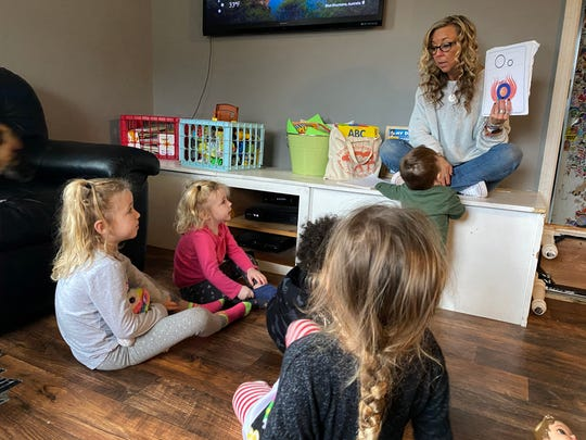 Child care provider Wendy Tilma leads morning circle time with her five charges for the day — ages 1 to 5 — at her home in Byron Center, Michigan.