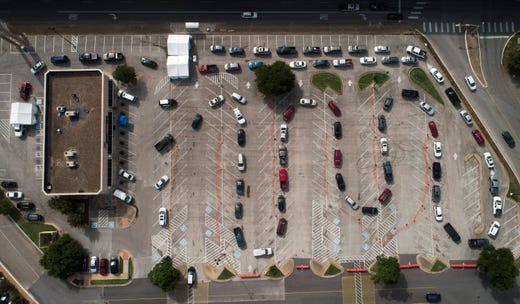 Dozens wait in their cars at a drive-through COVID-19 testing site at Community Care clinic at the Hancock Center in Austin, Texas, on Saturday June 27, 2020.