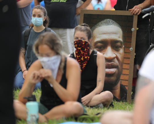 A protester holds a photo of George Floyd while listening to speakers at Patton Park before a march along Vernor Highway in southwest Detroit on Sunday.