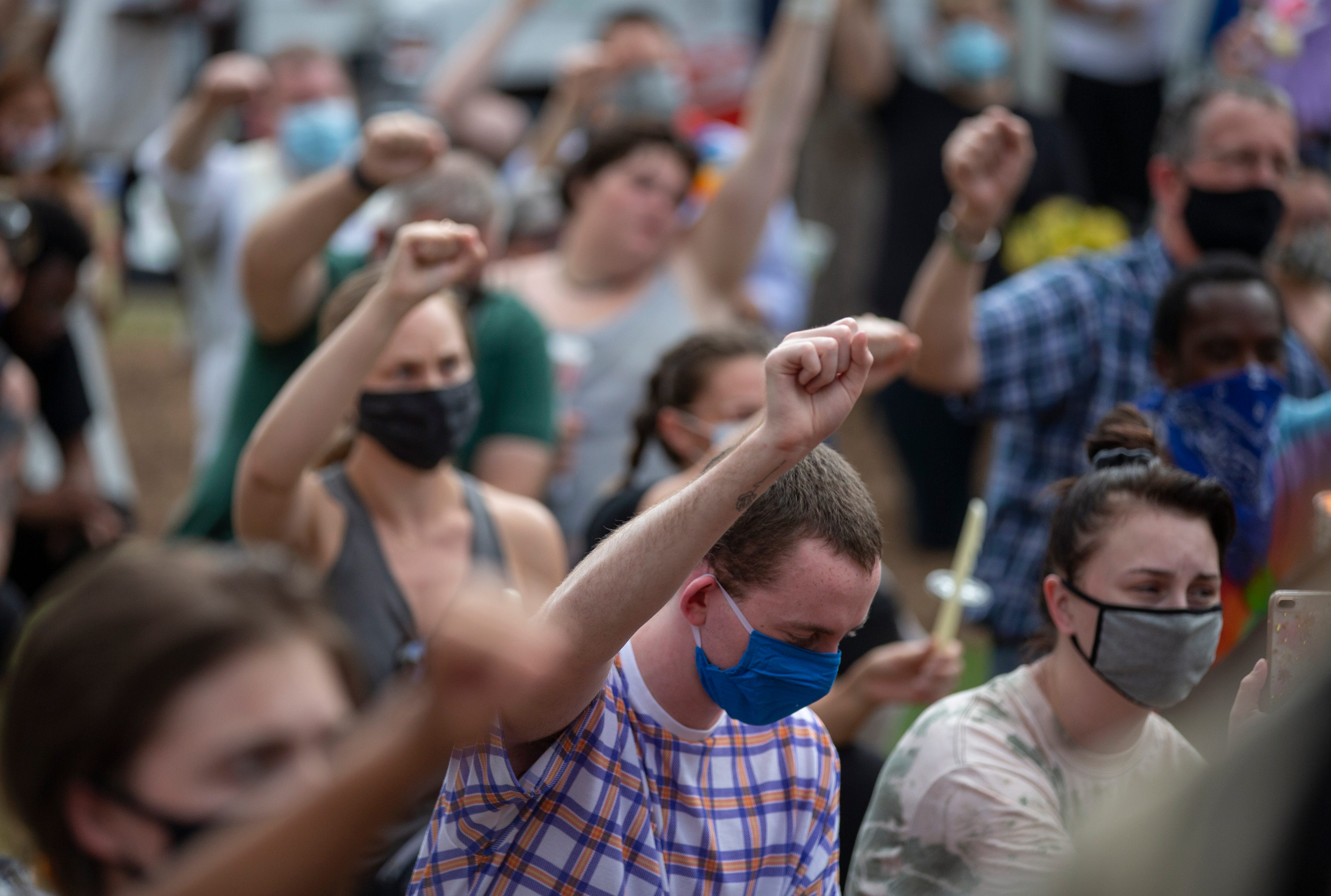 Mourners raise their fists in the air during a vigil for Tyler Gerth on June 28, 2020, a photographer who was shot and killed in Jefferson Square Park in Louisville, Ky.
