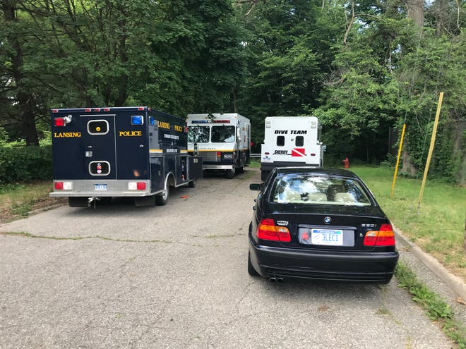Police vehicles parked on Roseneath Avenue in Lansing. A body was found in the Grand River nearby on Sunday, June 28.