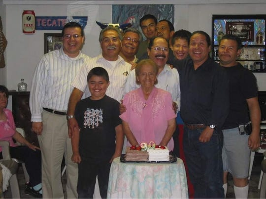 Sergio Vasquez, center, stands behind his mother, Pilar, during her 90th birthday celebration in this undated family photo.